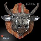 Steel head of a bull on a wooden, old board