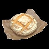 Круглая булка хлеба на вощеной бумаге